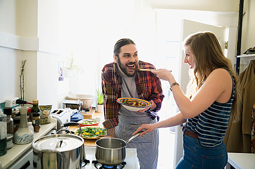 Couple cooking and tasting in kitchen