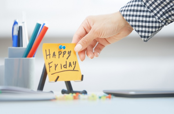 Human hand holding adhesive note with Happy Friday text